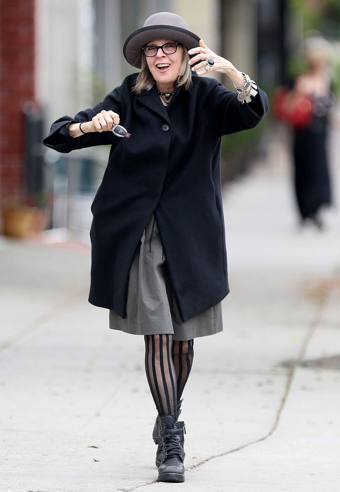 Hollywoodstar Diane Keaton kombiniert ihren schwarzen Eggshape-Mantel mit einem grauen Hut, gestreifter Strumpfhose und derben Schnürstiefeln.