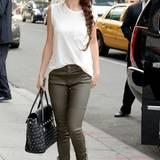 Mit olivgrüner Lederhose, schlichtem Top und nietenbesetzter Handtasche kreiert Selena Gomez einen modernen, rockigen Look.