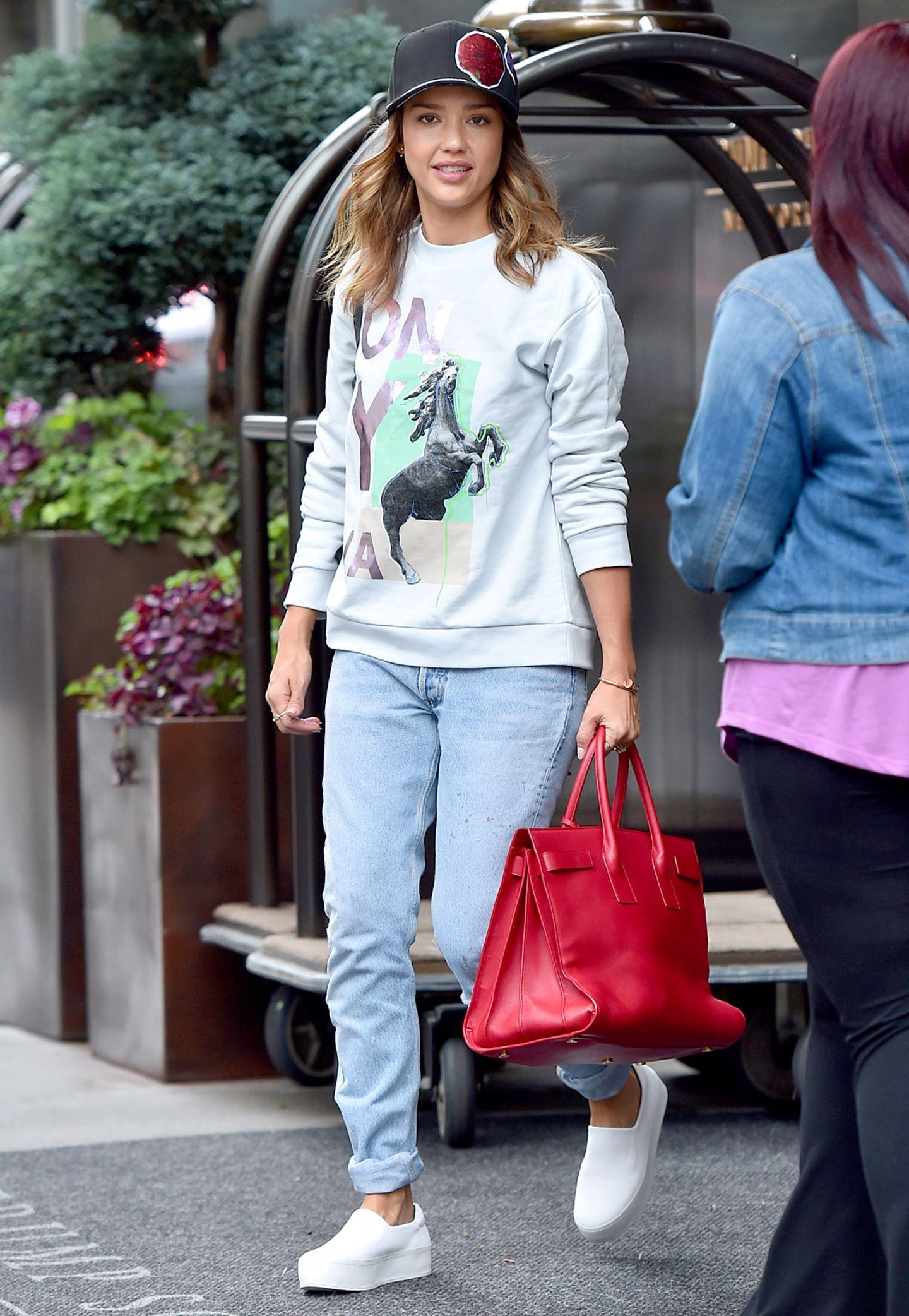 Von ihrer sportlichen Seite zeigt sich Jessica Alba in Print-Sweater und Plateau-Slippern.