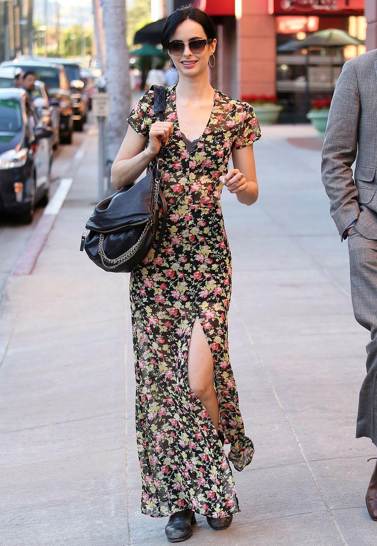 Ihre schmale Silhouette betont Krysten Ritter mit einem geblümten Maxi-Kleid, das ihre schlanken Beine zusätzlich durch einen hohen Schlitz zur Geltung bringt. Um den Blick nicht von dem Print abzulenken, trägt sie lediglich eine Handtasche und dezente Ohrringe dazu.