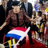 Eine sichbar gut gelaunte Königin Beatrix wird von Fahnen schwenkenden Kindern empfangen.