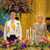 Beim Staatsbankett in Brunei gibt es einen Rausch aus Farben und Blumen. Máxima trägt ein silbernes, tailliertes Kleid mit langen Ärmeln und drapiertem Oberteil. Dazu kombiniert sie eine zarte Tiara aus Familienbesetz mit 27 Diamanten und mehr als 100 Karat.