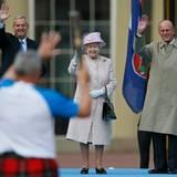 """9. Oktober 2013: Queen Elizabeth und Prinz Philip winken vor dem Buckingham Palast in London dem ersten Stabträger der """"Commonwealth Games"""", die 2014 im schottischen Glasgow stattfinden."""