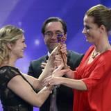 """Anna Loos und Jan-Josef Liefers übergeben Claudia Michelsen die goldene Kamera als """"Beste deutsche Schauspielerin""""."""