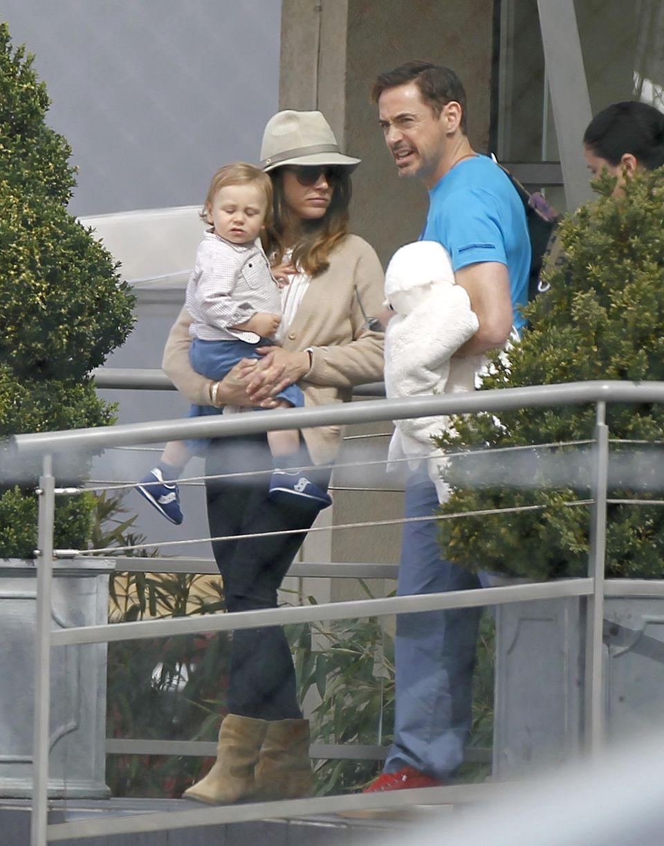 """16. April 2013: Während der Promotiontour für seinen neuen Film """"Ironman 3"""" ist Robert Downey Jr. mit Ehefrau Susan und Söhnchen Exon in Paris gerade auf dem Weg zum Privatjet, der die Familie nach London bringt."""