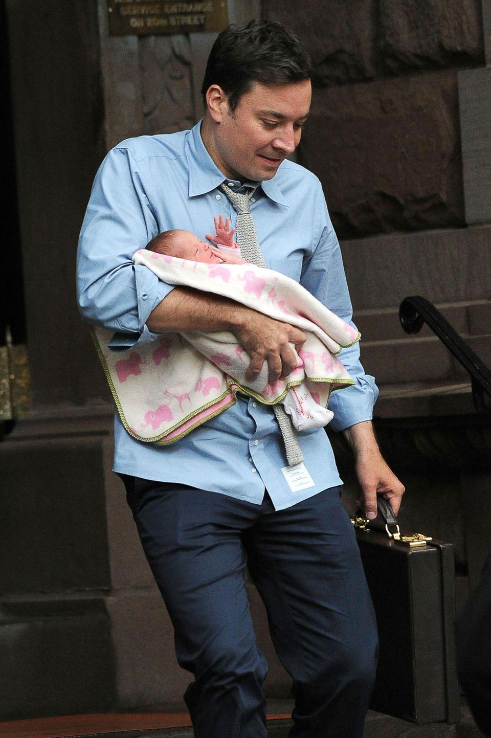 8. August 2013: In der einen Hand den Aktenkoffer, in der anderen Hand seine Tochter Winnie: Jimmy Fallon verlässt sein New Yorker Apartment.