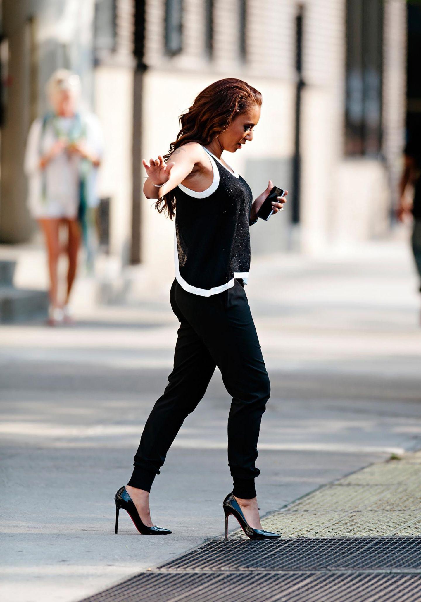 20. August 2013: Mel B balanciert in ihren hohen Schuhen vorsichtig über ein Lüftungsgitter.