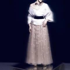 Langes Kleid aus zarter Spitzenstickerei, von Valentino. Kimonojacke von Regent x Kostas Murkudis, Gürtel von Maison Martin Margiela. Collier von Prim by Michelle Elie, Ring von Chopard.