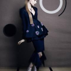 Lange Schößchenjacke mit Stickereien und dazu passendem Plissee-Minirock, von Christian Dior. Wadenlanger Rock von Masha Ma, Butterfly-Kette von Chopard, Schuhe und Ledersöckchen von Prada.