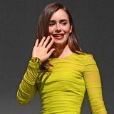 In einem neongelben Kleid von Versace leuchtet Lily Collins sogar auf einer dunklen Bühne.