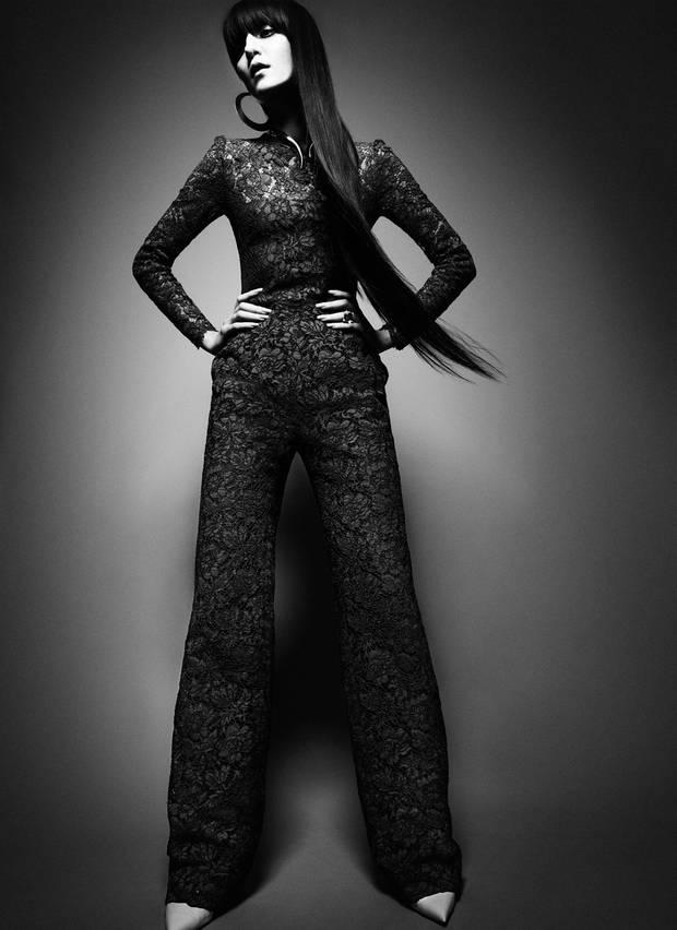 Jumpsuit aus grüner Spitze, von Valentino. Maxi-Creolen von H&M, goldenes Collier von Giuseppe Zanotti. Ring mit weißem Topas und Brillanten, von Pomellato. Cremefarbene Lack-Pumps von Louis Vuitton