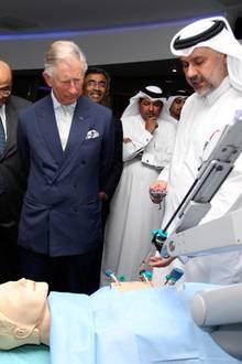 Im Technologiezentrum zeigt Professor Abdullah Al Ansari Prinz Charles an einer Puppe, wie mit Mikrorobotik am Herzen operiert wird.