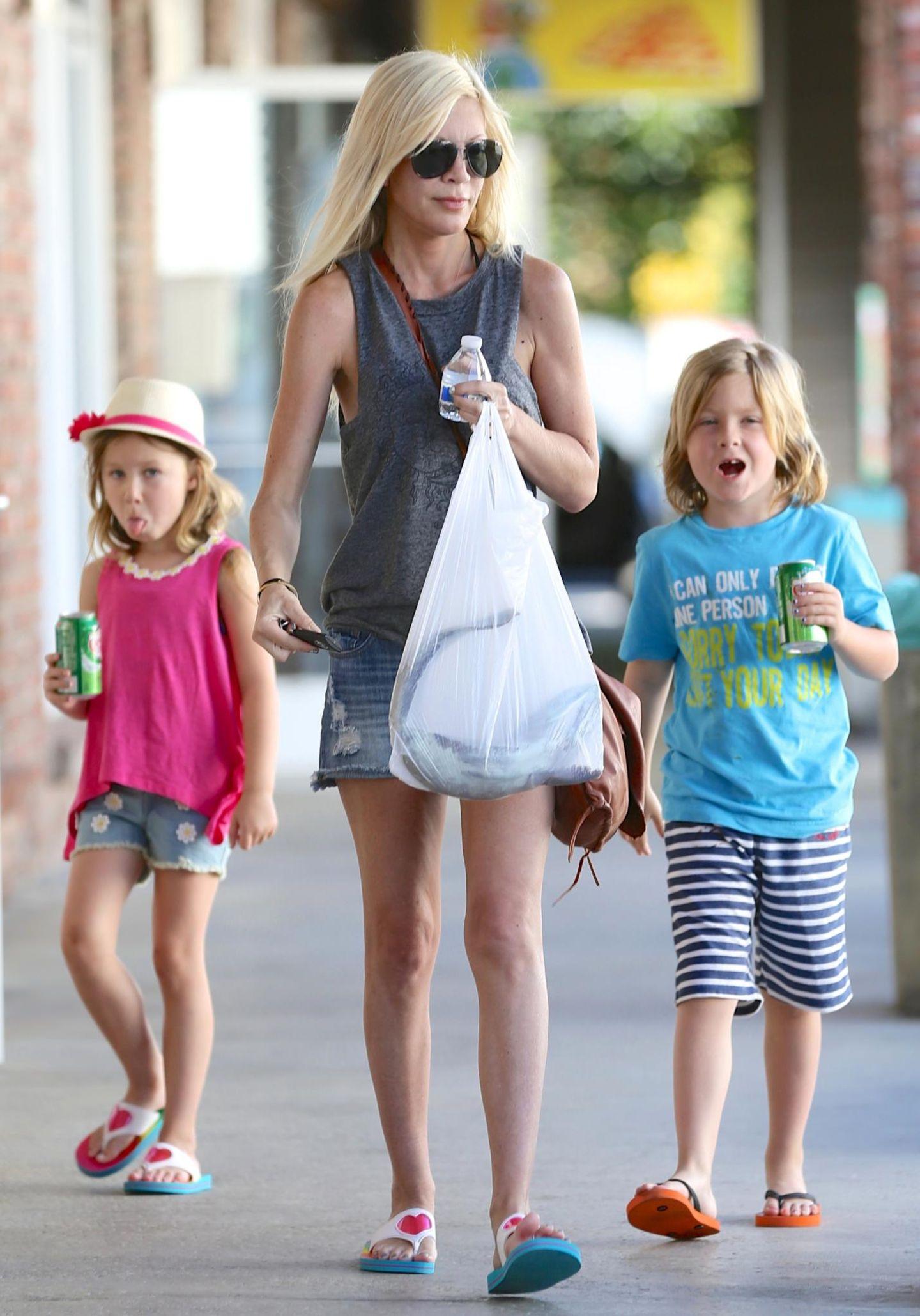April 2014  Beim Besuch der thailändischen Massage bekommt Tori Spelling eine Tüte mit frischem Fisch geschenkt und bringt sie zusammen mit ihren Kindern Liam und Stella zum Auto.