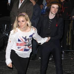 """Auf dem roten Teppich trug Sienna Miller noch ein bodenlanges weißes Kleid und darüber eine nietenbesetzte Lederjacke. Für die Party danach entscheidet sie sich für einen löchrigen """"Anarchy In The UK""""-Pullover. Ihr Freund Tom Sturridge hat sich hingegen nicht umgezogen."""