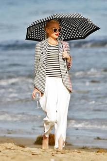 Gwen Stefani verbringt den Memorial Day bei der Party von Joel Silverman. Sie genießt am Strand von Malibu ein Glas Wein und schützt sich mit einem farblich auf ihr Outfit abgestimmten Schirm vor der Sonne.
