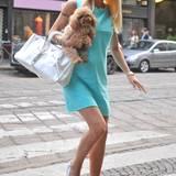 Gut gelaunt, mit Hund und Prada-Tasche besucht die schwangere Moderatorin ein Lokal. Ihr hellblaues A-Linien-Kleid versteckt den wachsenden Babybauch ziemlich gut.