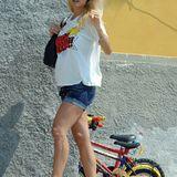 Zum weiten Comic-Shirt kombiniert die werdende Mutter eine kurze Jeansshorts und schlichte weiße Turnschuhe.