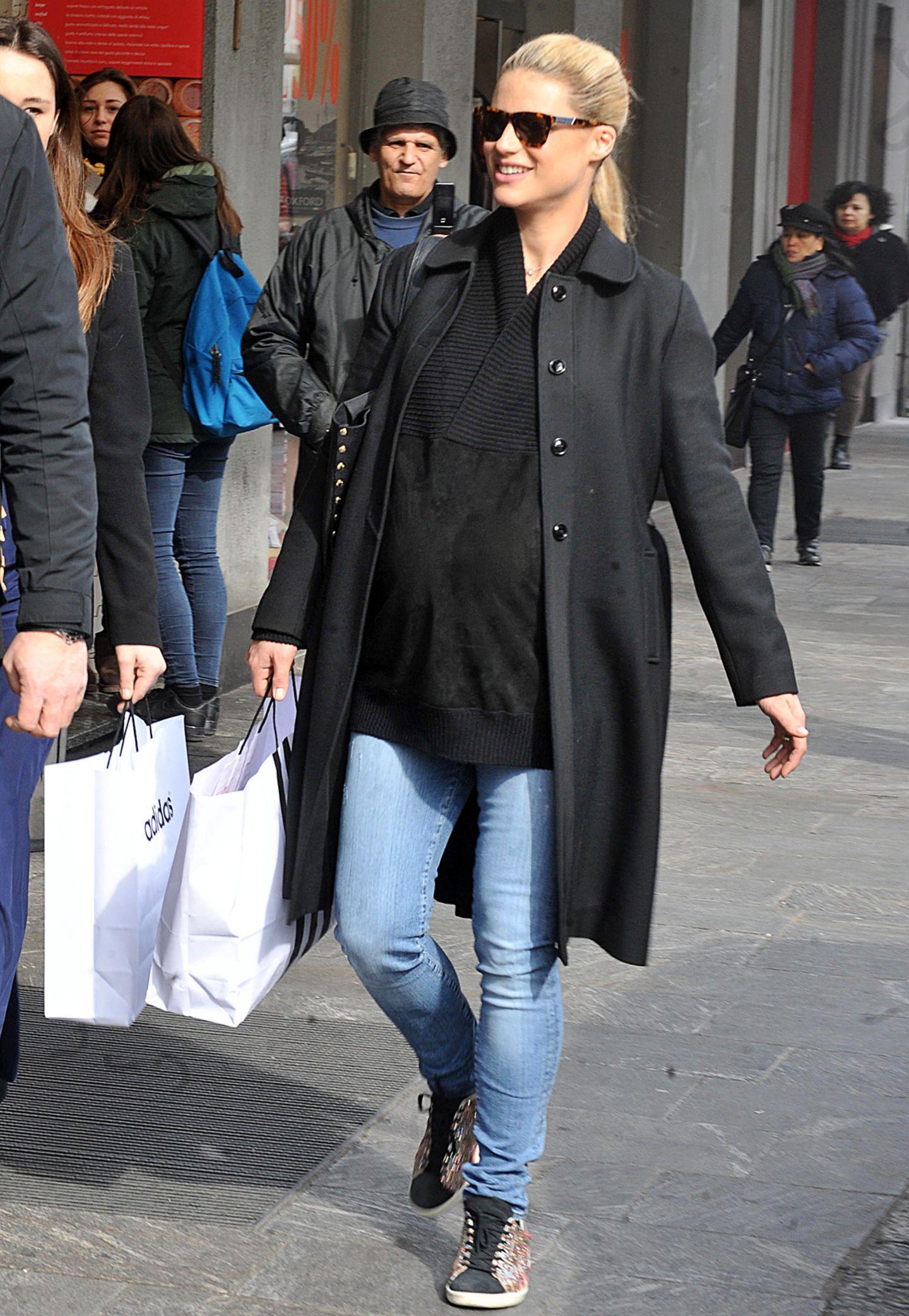 Der schwarze Wollpullover mit V-Kragen hält Michelle Hunzikers runden Bauch warm, die Jeans und bunten Sneaker sind für eine Shoppingtour genau das Richtige.