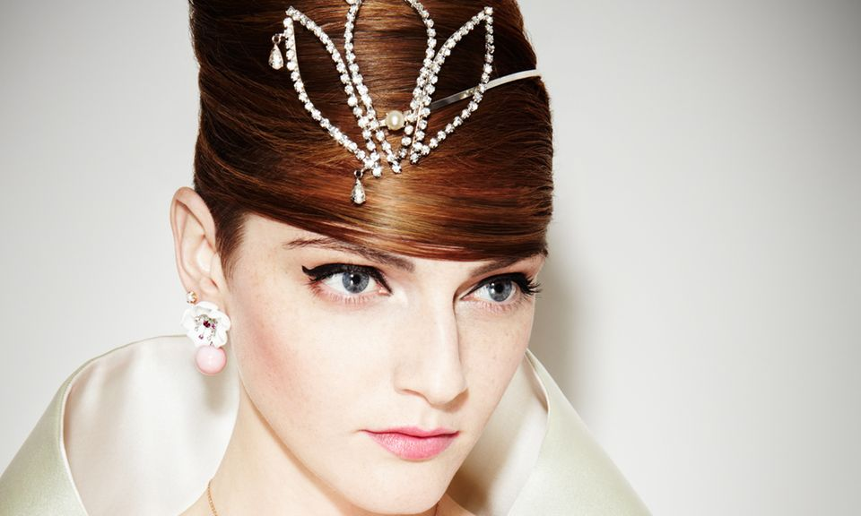 Miss Glückskeks trägt Ohrringe aus Weißgold und Opal, von Piaget. Blütenkette und -ring von Montblanc. Schmale Bandringe von Xen, großer Diamantring von Cartier. Charm-Armbänder von Dodo. Diadem von Swarovski. Seidenstola von Prada