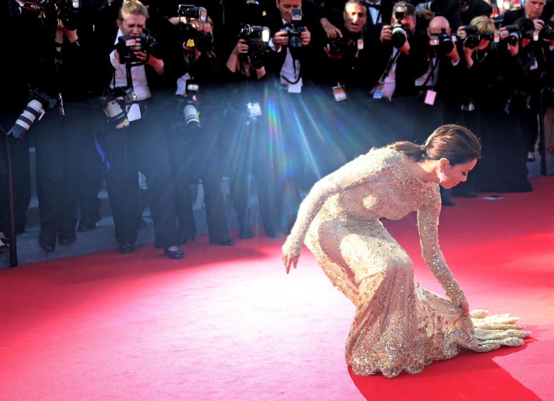 Eva Longoria müht sich mit der Schleppe ihres Kleides ab.