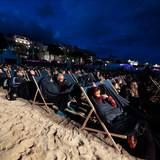 Dick eingepackt mummeln sich Festival-Zuschauer am Strand in ihre Liegestühle.