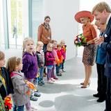 Das niederländische Königspaar begrüßt, gemeinsam mit Kanzlerin Merkel, eine Gruppe von Kindern, die sogar wuschelige Winkelemente in den Landesfarben mitgebracht haben.