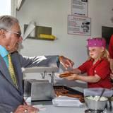 """Prinz Henrik bekommt an einem typisch dänischen Imbisswagen eine """"risted pølser"""", eine Bratwurst, serviert. Wie man sieht, hätte die junge Wirtin ihrem royalen Gast auch ein Hot Dog zubereiten können."""