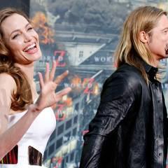 Angelina Jolie und Brad Pitt treten vor die Plakatwand.