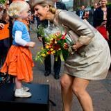 Vor dem Rathaus von Haarlem (Provinz Noord-Holland) gibt es Blumen für die Königin. Und wie es sich für so einen Anlass gehört, hat das kleine Mädchen einen farblich passendes Outfit angezogen. Und damit sich die Königin, die zum kurzen Rock wieder hohe Schuhe trägt, nicht zu weit herunter beugen muss, steht das Mädchen auf einem kleinen Podest.