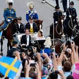 Viele Schaulustige haben sich am Straßenrand versammelt, um dem Brautpaar zu winken.