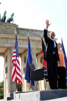 Der US-Präsident, die Bundeskanzlerin und Berlins Bürgermeister Klaus Wowereit begrüßen die Menschen vor dem Brandenburger Tor.