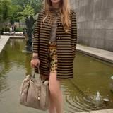Mustermix deluxe: Zum schwarz-goldenen Mantel trägt dieser Modefan goldene Plateau-Sandalen und Shorts mit Palmen-Print.