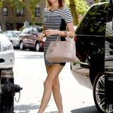 Auch Taylor Swift mixt gerne Luxus mit Kleidung von der Stange und trägt zur Prada Tasche ein süßes, gestreiftes Kleid von Topshop.