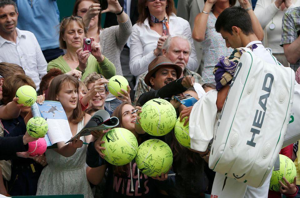 Nachdem er den Deutschen Florian Mayer geschlagen hat, sind die Fans ganz wild auf Autogramme des Serben Novak Djokovic.