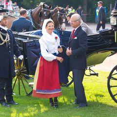 Königin Silvia, Prinz Carl Philip und König Carl Gustaf kommen mit der Kutsche zum Festplatz.