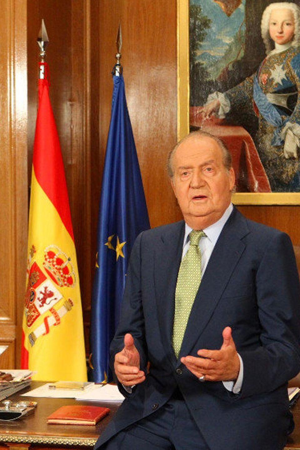 Die Weihnachtsansprache 2012 hält König Juan Carlos von Spanien ganz lässig an seinen Schreibtisch im Zarzuela-Palast in Madrid gelehnt. Neben Zeitungen und Unterlagen stapeln sich Bücher auf dem Tisch. Links neben dem Gemälde hinter ihm stehen die spanische und europäische Flagge vereint.