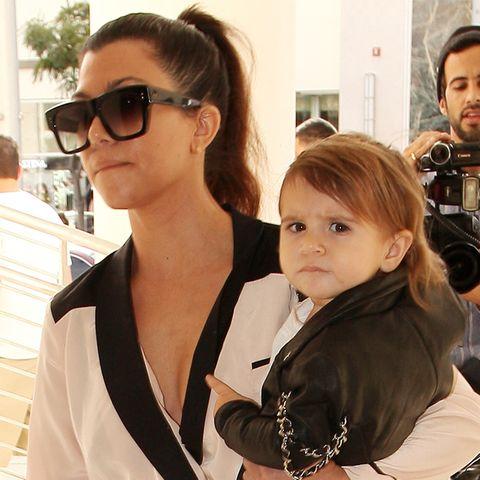 Mini-Fashionista Penelope lässt sich von Mama Kourtney Kardashian in cooler Lederjacke mit Ketten-Details tragen.