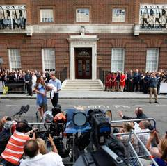 """Catherine und William stehen den wartenden Reportern Rede und Antwort und sind sogar zu Scherzen aufgelegt. Angesprochen auf den feinen Haarflaum, den das Baby auf dem Kopf trägt, sagt William: """"Er hat mehr als ich, zum Glück."""""""
