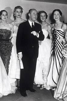 """Die Anfänge einer Erfolgsgeschichte: Firmengründer Christian Dior zeigt sich im Jahr 1950 umgeben von seinen Entwürfen. Nach den entbehrungsreichen Jahren des Krieges ist es das 1946 gegründete Haus Dior, das mit dem """"New Look"""" eine neue, verschwenderische Silhouette an die Frauenkörper schneidert. Die Empörung ist groß - doch die neue Weiblichkeit wird zu einem heißbegehrten Klassiker. Der Startschuss einer Weltkarriere."""