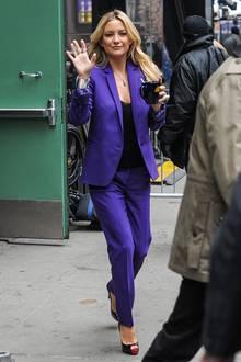 Im violetten Hosenanzug und mit turmhohen Peeptoe-Stilettos spaziert die Schauspielerin - samt einer Tasse Kaffee - aus einem TV-Studio.