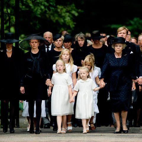 Geschlossen und sich an den Händen haltend betritt die niederländische Königsfamilie den Friedhof.