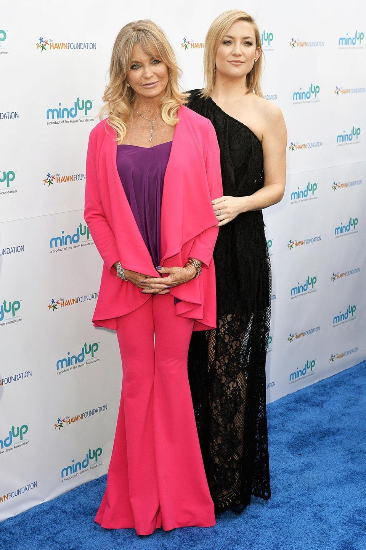 """Goldie Hawn ist im pinken Schlaghosen-Anzug auf ihrer eigenen Charity-Gala """"Goldie's Love In For Kids"""" in Beverly Hills farblich ein ganz besonderer Blickfang. Ihre Tochter Kate Hudson präsentiert sich auf dem blauen Teppich mit ihrem One-Shoulder-Spitzenkleid dagegen eher zurückhaltend."""
