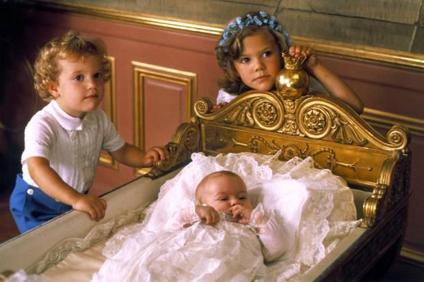 Prinzessin Victoria, die älteste der drei Königskinder, und ihr jüngerer Bruder Carl Philip stehen an der Wiege ihrer kleinen Schwester Madeleine.