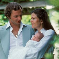 Königin Silvia trägt die kleine Prinzessin Victoria auf dem Arm.