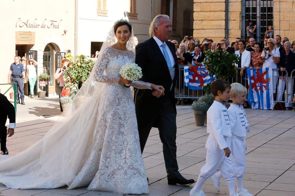 Am Arm ihres Vater schreitet die strahlende Prinzessin Claire in Richtung Basilika. Vor ihr gehen Prinz Gabriel und Prinz Noah von Luxemburg, die als Brautkinder dabei sind. Die beiden sind die Söhne von Prinzessin Tessy und Prinz Louis.