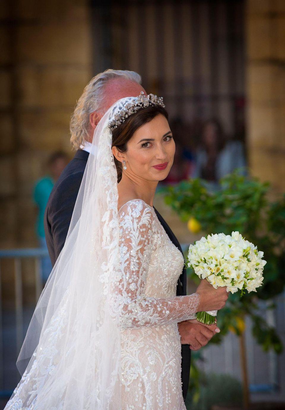 Prinzessin Claire trägt ein zartes Diadem im Haar, das den üppig verzierten Schleier hält. Ihr Hochzeitkleid ist eine Kreation von Elie Saab aus cremefarbener Seide, das mit Silber, Kristallen, Pailetten und Perlen verziert ist.