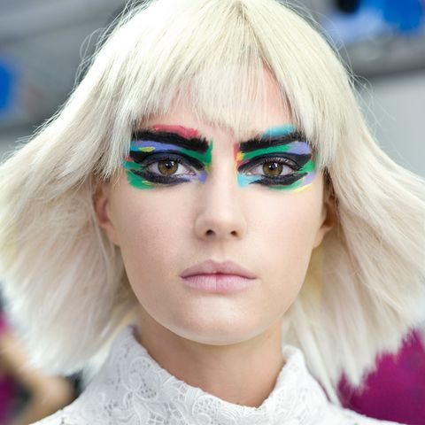 Ungewohnt farbenfroh und rockig schickte Chanel seine Models auf den Laufsteg. Das extravagante Augen-Make-up wird durch platinblonde Perücken noch betont.