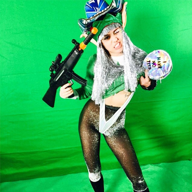 Autsch! Der glitzernde Cowboy-Kobold im Borat-Look und mit Spielzeug-Pumpgun ist wohl Mileys Idee von festlichem Weihnachtsstyling.
