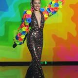 Miley In The Sky With Diamonds?! Welche fragwürdigen Substanzen der Designer dieses Outfits vor dem kreativen Prozess konsumierte, ist leider nicht überliefert. Irgendwie erinnert der Flower-Power-Overall-Albtraum aber an die feuchtfröhlichen Schlager-Partys, die wir Deutschen so schrecklich gerne feiern.