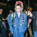Mit der überweiten, mit Stickern übersäten Jeansjacke über dem Denim-Jumpsuit könnte Miley Cyrus geradewegs aus den Achtziger kommen. Und mitdem Dreadlock-Haarteil setzt sie sich selbst noch ganz persönlich die haarige Grusel-Krone auf.
